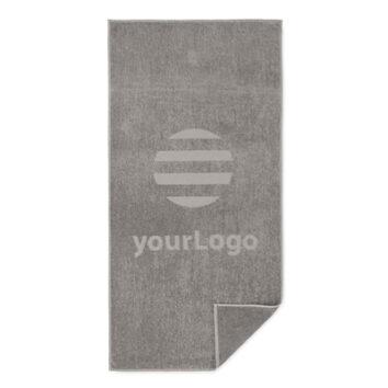 Das Logodesign erscheint als flache Fläche, auf der die Frotteeschlaufen fehlen. Dieser Prozess erzeugt exzellente Prägedesigns. Die Rückseite des Handtuchs behält die Standard-Frottierstruktur bei.